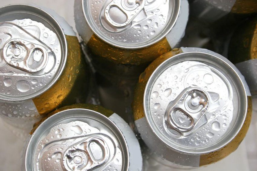 Six pack cans of beer resting on ice