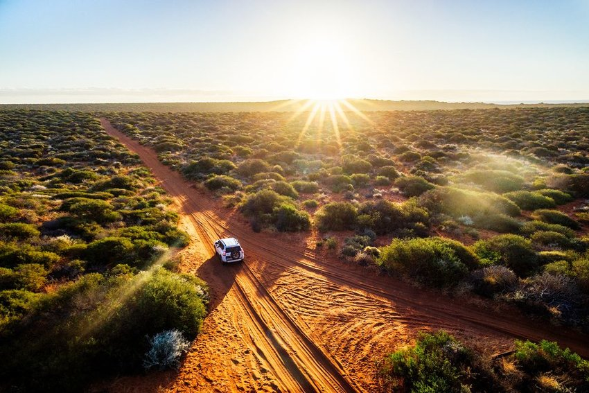 Car driving on dirt road in the Australian outback