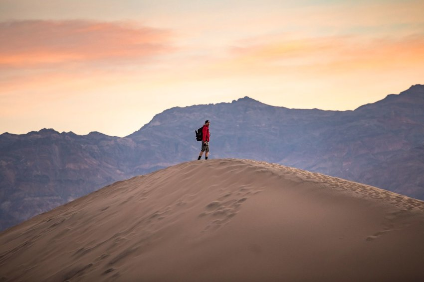 Person standing on the top of a sand dune in Death Valley