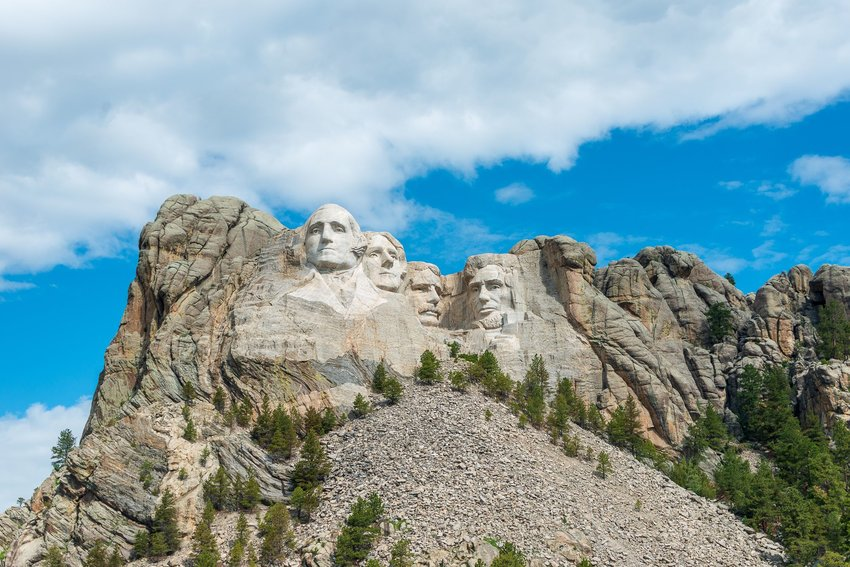 Mount Rushmore with clouds in a blue sky in the background