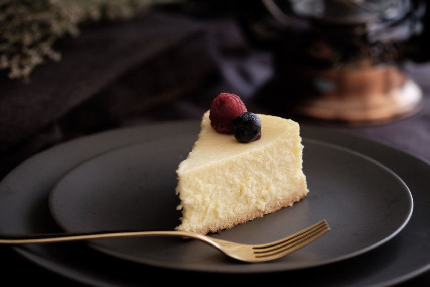 Slice of cheesecake on a black plate with berries on top