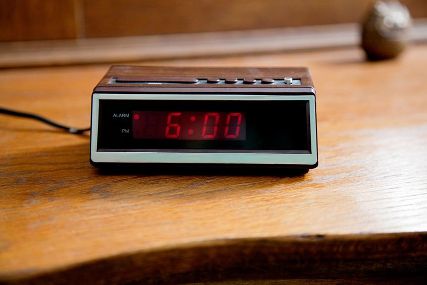 Digital alarm clock on wooden table