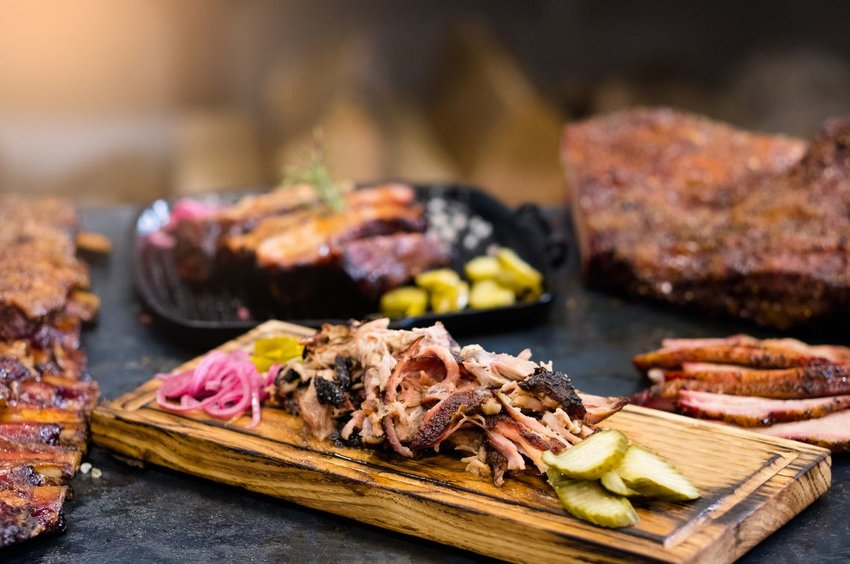 Smoked pulled pork served with pickles on wooden board