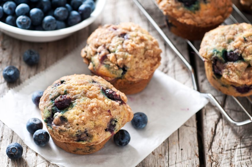 Blueberry muffins with a bowl of blueberries in the background