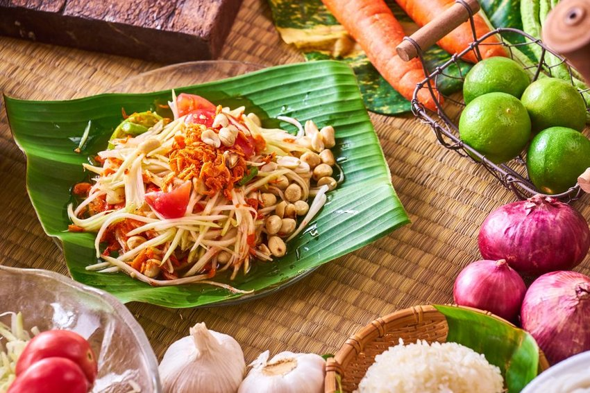 Som Tam in a green leaf bowl with ingredients all around
