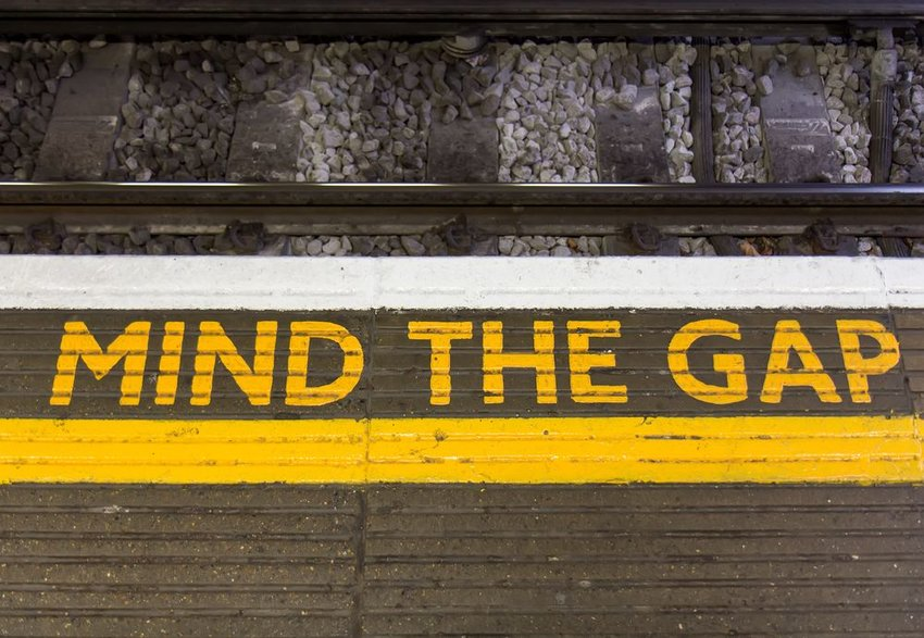 """Mind the Gap"" printed on ground before train tracks"