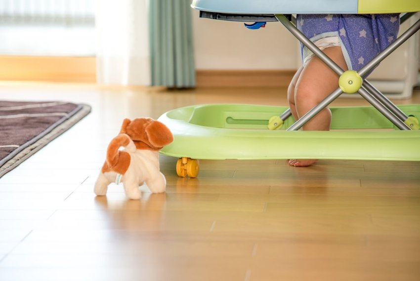 Baby in a baby walker with toy on the wood floor