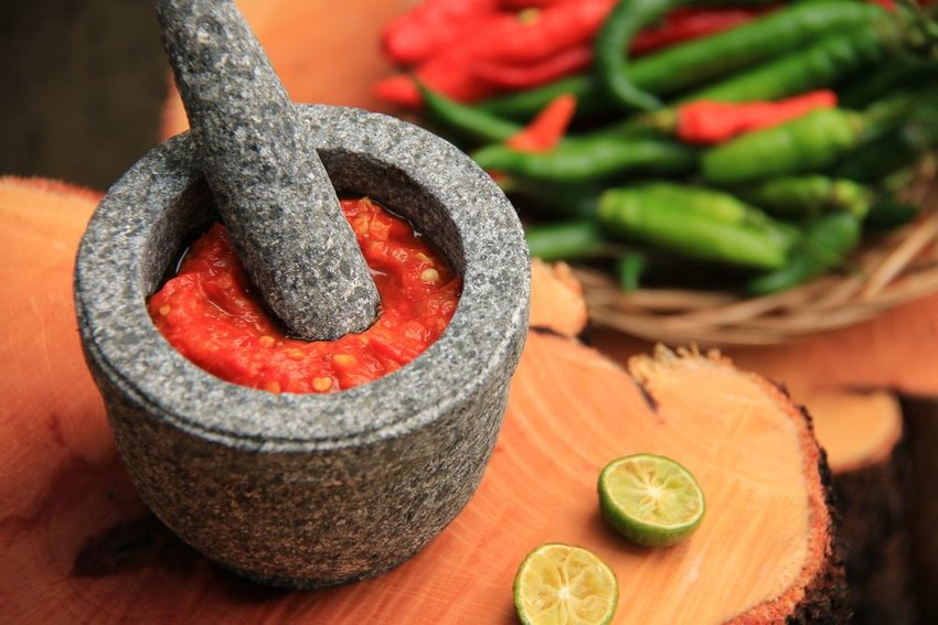 Sambal in a bowl with peppers in the background