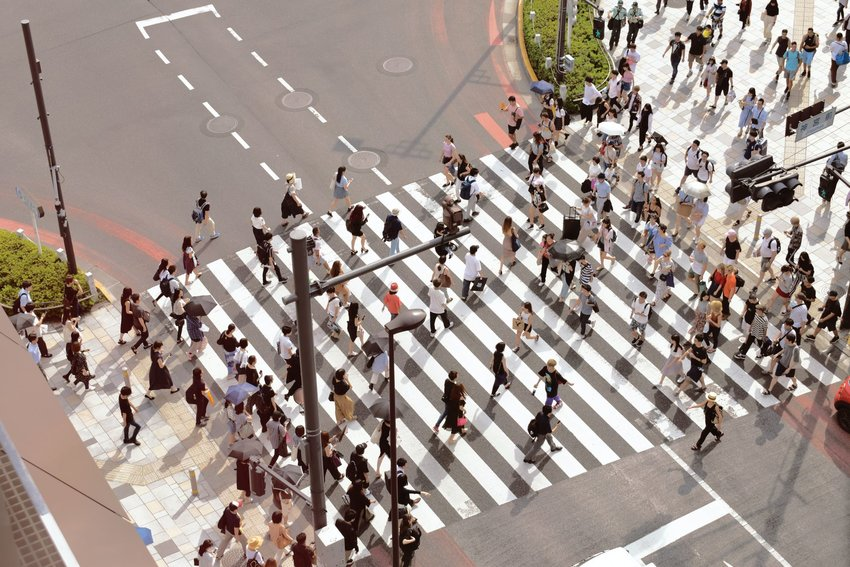Aerial view of people walking across crosswalk