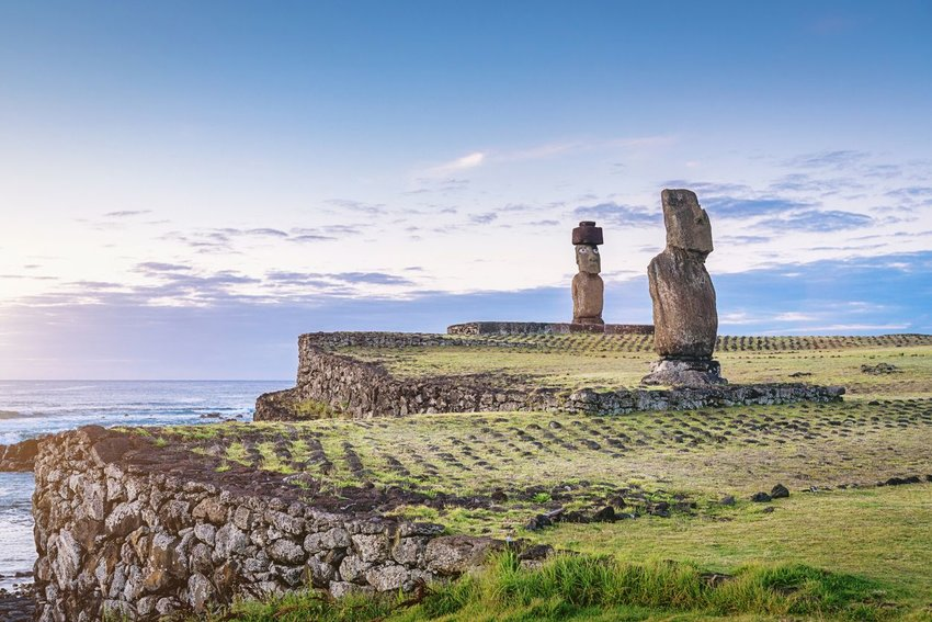 Two statues in Easter Island with the sunset and ocean in the background