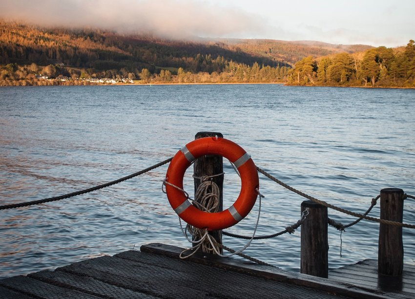 Life preserver on a dock with water in the background