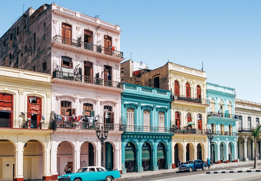 Old fashioned cars parked in front of colorful buildings in Cuba