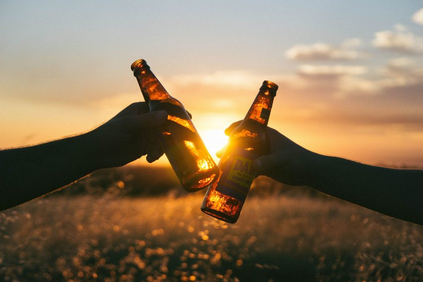 Two people clinking their beer glasses at sunset