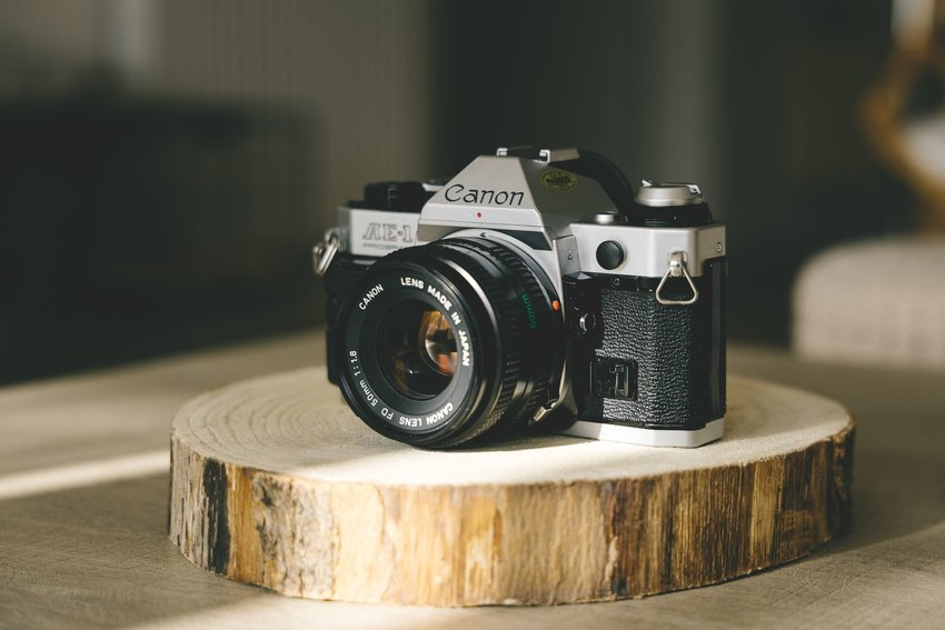 A film camera resting on a slab of wood on a table