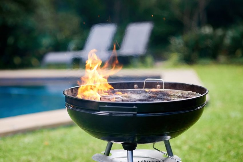 Fire coming out of top of barbecue grill with pool and lounge chairs in background