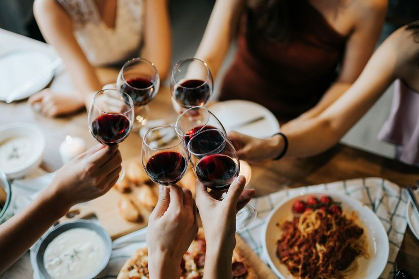 Group of people toasting with red wine