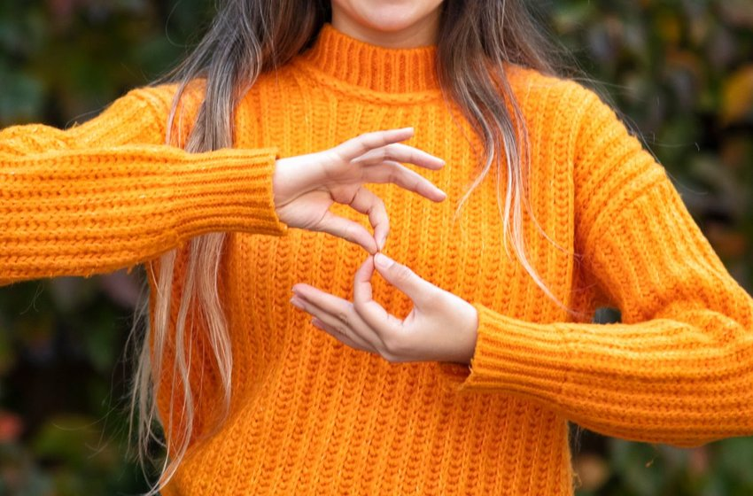 Woman in a orange sweater doing sign language