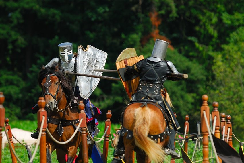Two people jousting on horses
