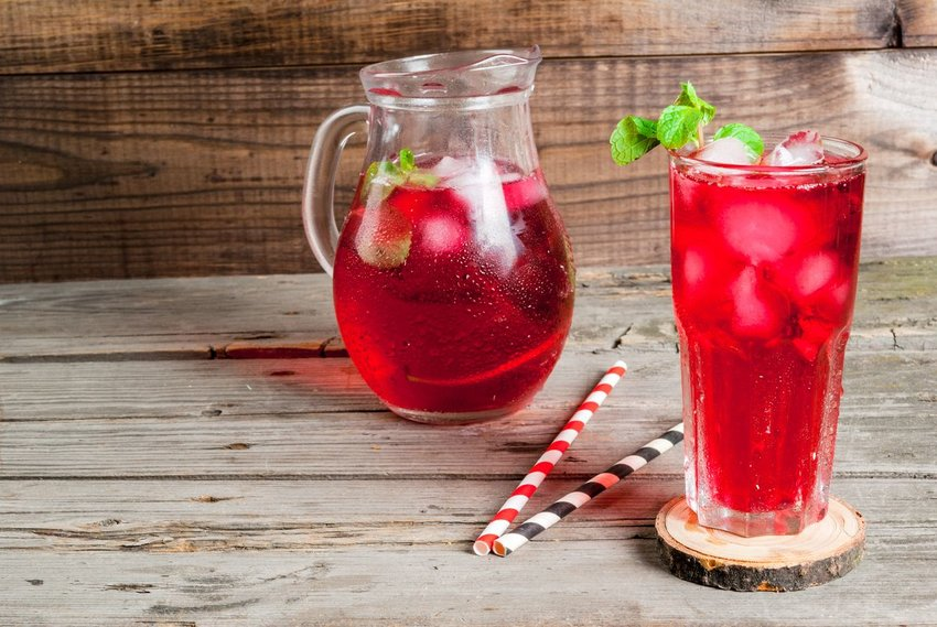 Kool aid in a pitcher with a full glass and paper straws on wooden table