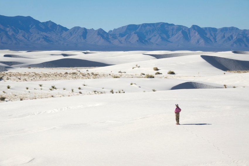 Person standing in White Sands National Park in New Mexico with mountains in the background
