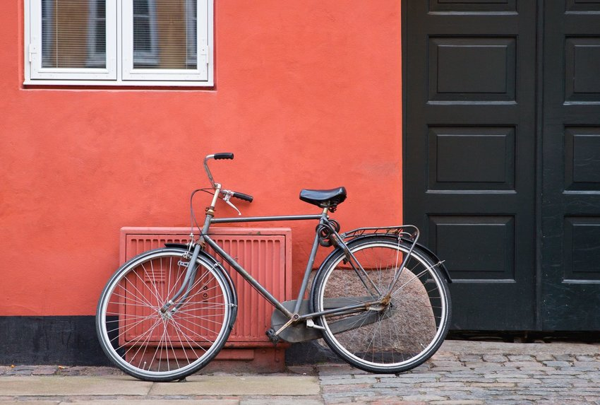 A black bicycle leaning up against a red wall