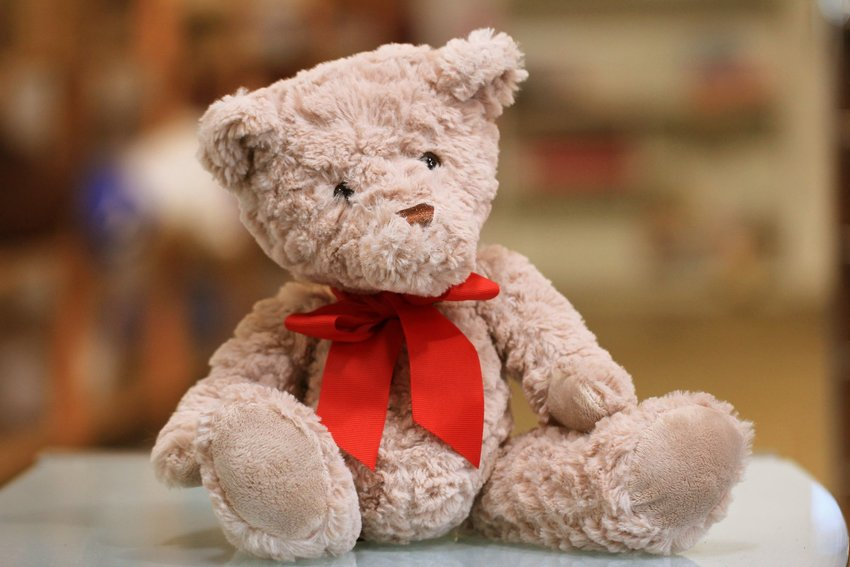 A teddy bear with a red ribbon tied around his neck