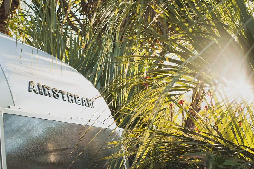Front of an Airstream trailer with palm trees and sun in the background