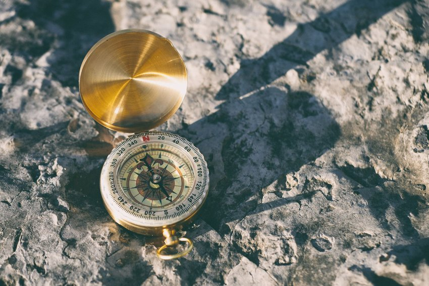Golden compass sitting on a rock