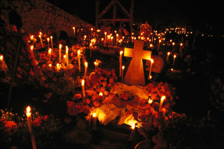 Graveyard at night with candles, flowers, and other decorations for Dia de Los Muertos