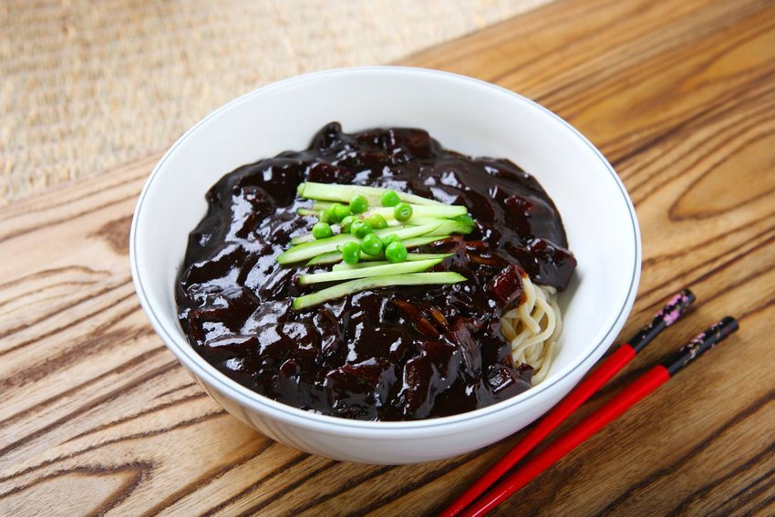 Bowl of jajangmyeon with chopsticks on a wooden table