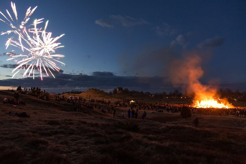 Walpurgis Night celebrations with fireworks, revelers and bonfire in a grassy field at night