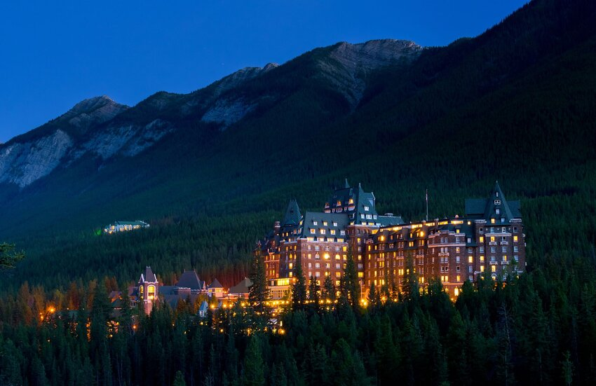 Fairmont Banff Springs resort at night, surrounded by mountains and forest