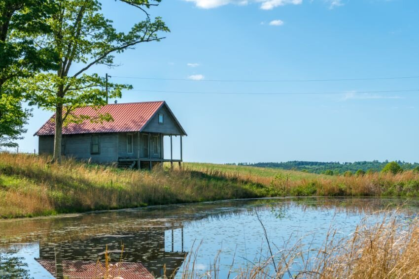 Rural old house barn reflected in pond water in northwest Arkansas.