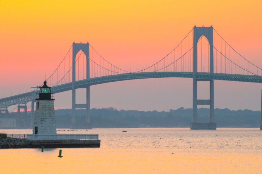 Newport Harbor Lighthouse and the Newport Bridge at sunset.