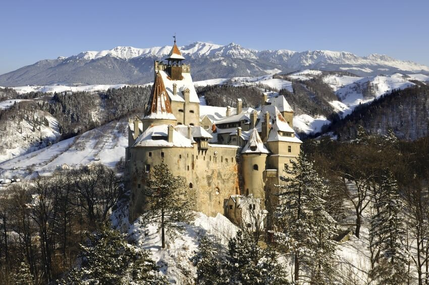 Bran Castle in winter with snow and Bucegi mountains.