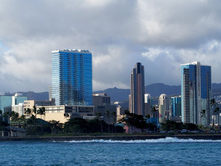 Wave crashes against rock seawall at Kaka`ako Waterfront Park with Honolulu in the distance
