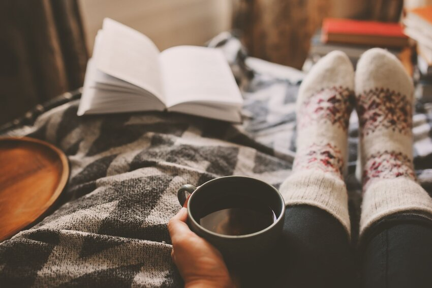 Person on bed with cozy socks, book, and cup of tea