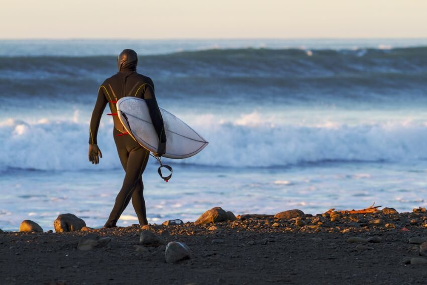 Surfer wearing a full body wetsuit, hood, booties and gloves for cold water surfing.