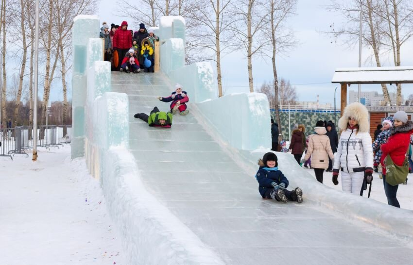 Children is riding on an ice slide.