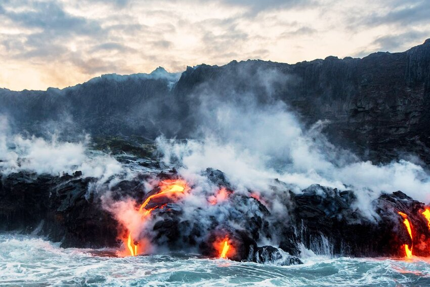 Molten lava flowing into the Pacific Ocean on Big Island of Hawaii at sunrise.