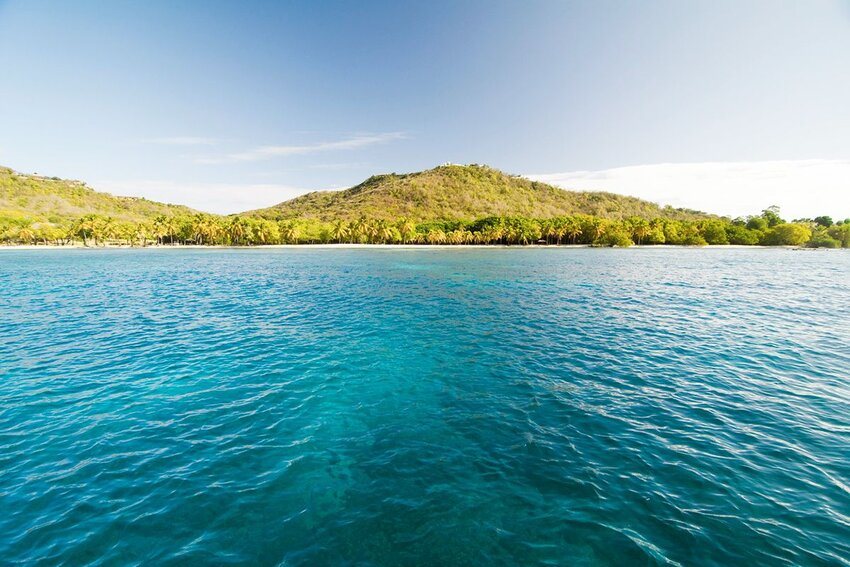 View over to palms and beach of Mustique Island, St.Vincent and Grenadines, West Indies.