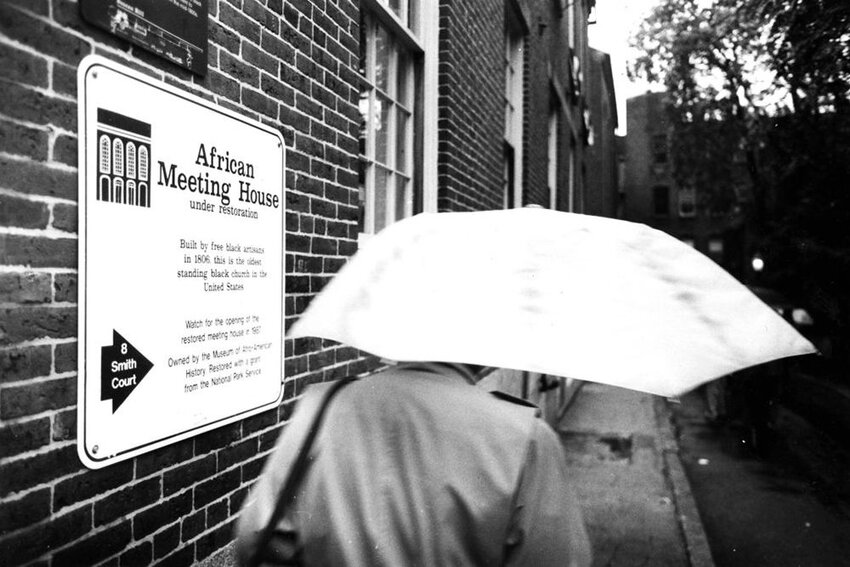 People arrive under under umbrellas at the African Meeting House on Beacon Hill in Boston.