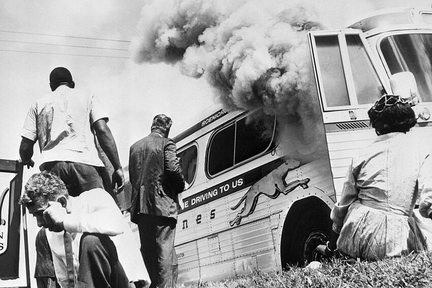 "Passengers of this smoking Greyhound bus, some of the members of the ""Freedom Riders""."