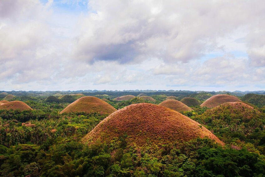 Chocolate Hills under blue sky in the Philippines aerial view by drone.
